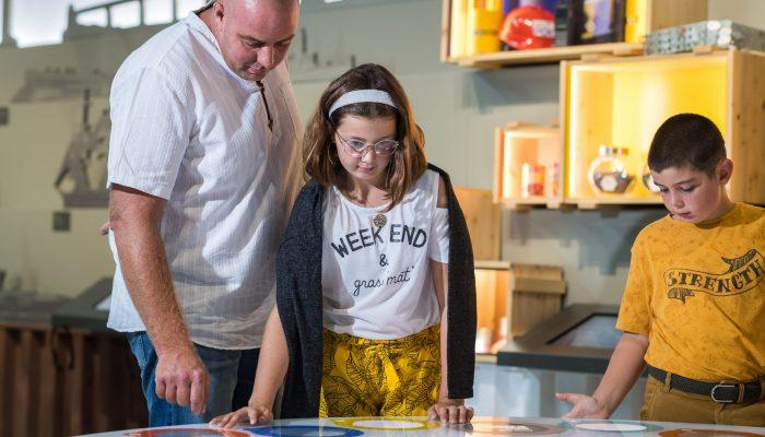 famille adultes et enfants autour de la table des industries espace Comprendre Terre d'estuaire